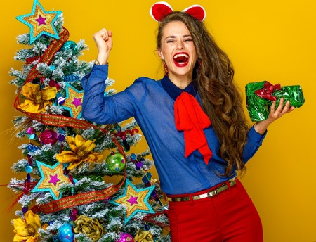 Festive season. smiling modern woman near Christmas tree on yellow background with wrapped as a gift photo camera rejoicing