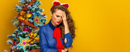 축제의 계절. 노란색 배경에 고립 된 크리스마스 트리 근처의 스트레스를받은 우아한 여자의 초상화