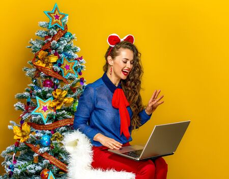 Festive season. smiling modern woman near Christmas tree isolated on yellow background having video chat on laptop Stock Photo