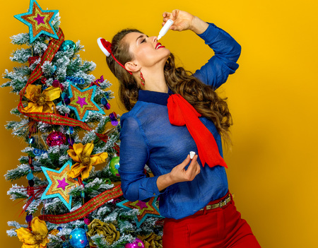 Festive season. trendy woman near Christmas tree on yellow background using nasal spray