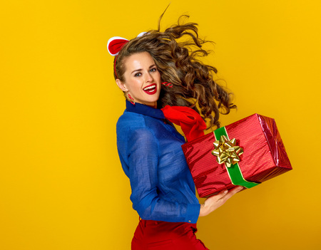 Festive season. happy stylish woman isolated on yellow background with red present box running