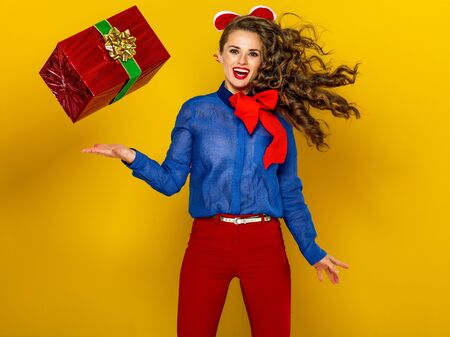 Festive season. smiling stylish woman isolated on yellow background with red present box jumping