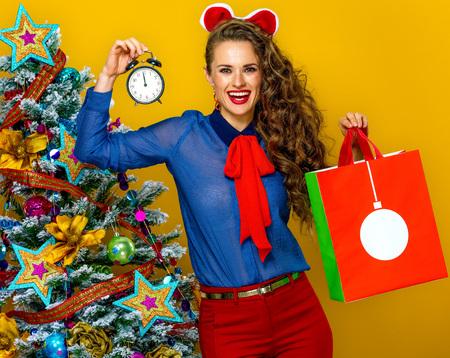Feestelijk seizoen. lachende trendy vrouw in de buurt van de kerstboom geïsoleerd op gele achtergrond met kerst boodschappentas wekker weergegeven