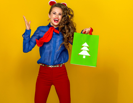 Festive season. smiling modern woman  isolated on yellow background with Christmas shopping bag jumping