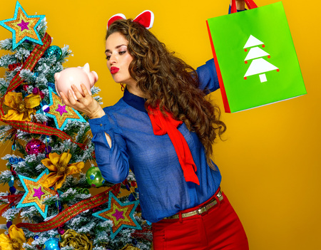 Festive season. stylish woman near Christmas tree isolated on yellow background with Christmas shopping bag and piggy bank