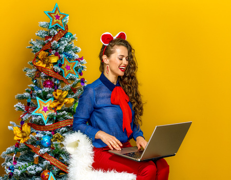 Festive season. happy stylish woman near Christmas tree on yellow background using laptop
