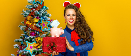 Festive season. happy trendy woman near Christmas tree isolated on yellow background showing present box and piggy bank with an euro bill
