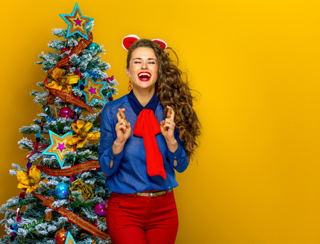 Festive season. smiling trendy woman near Christmas tree isolated on yellow background with crossed fingers Stock Photo