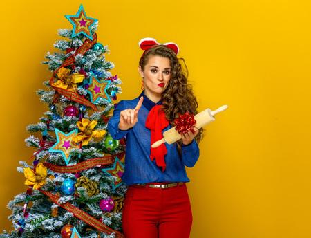 Festive season. modern woman near Christmas tree on yellow background unhappy with present