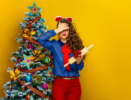 Festive season. unhappy young woman near Christmas tree on yellow background holding unwanted present
