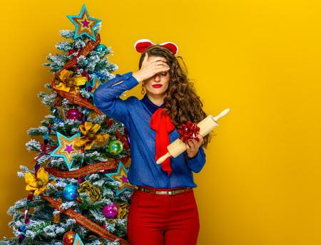Temporada festiva. mujer joven infeliz cerca de árbol de Navidad sobre fondo amarillo con regalo no deseado
