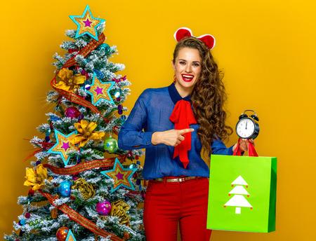 Feestelijk seizoen. lachende trendy vrouw in de buurt van de kerstboom geïsoleerd op gele achtergrond met kerst boodschappentas wijzend op wekker Stockfoto