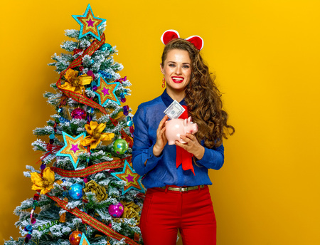Festive season. happy stylish woman near Christmas tree isolated on yellow background putting dollar bill in piggy bank