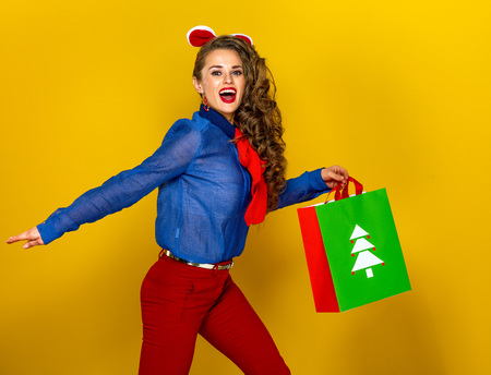 Festive season. smiling modern woman isolated on yellow background with Christmas shopping bag running
