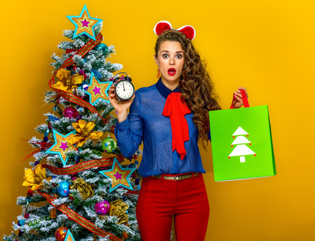 Feestelijk seizoen. verraste elegante vrouw dichtbij Kerstboom op gele achtergrond met Kerstmis het winkelen zak en wekker