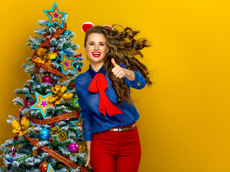 Festive season. happy trendy woman near Christmas tree isolated on yellow background showing thumbs up