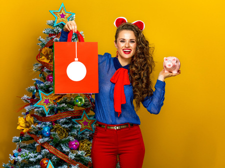 Festive season. smiling elegant woman near Christmas tree isolated on yellow background showing Christmas shopping bag and piggy bank Stock Photo