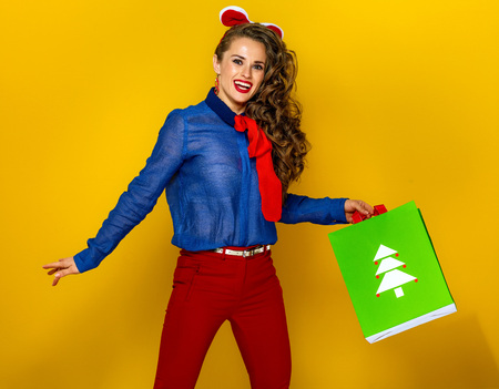 Festive season. happy trendy woman near Christmas tree on yellow background with Christmas shopping bag jumping