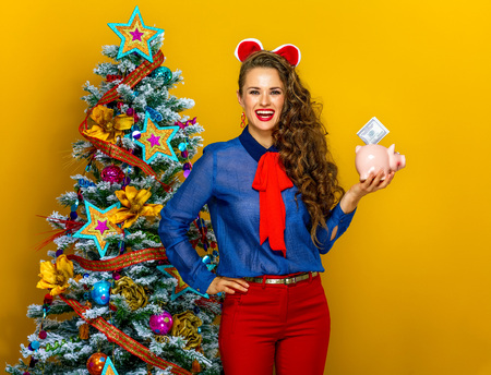 Festive season. smiling stylish woman near Christmas tree on yellow background showing a piggy bank with a dollar bill
