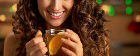 Closeup on happy young woman with cup of ginger tea Stock Photo