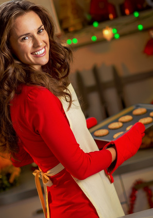 Happy young housewife with pan of christmas cookies Stock Photo