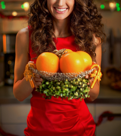 Closeup on happy young housewife showing plate of oranges Stock Photo