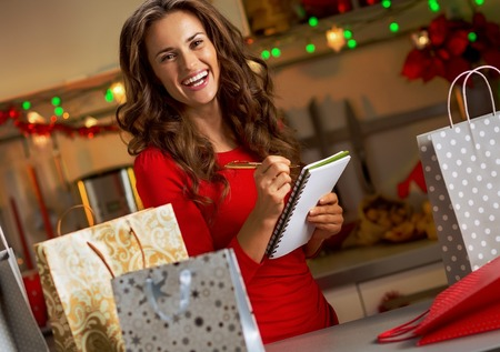 Happy young woman checking list of christmas presents 스톡 콘텐츠