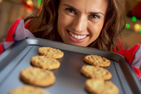 크리스마스 쿠키와 함께 냄비를 보여주는 행복 젊은 주부 스톡 콘텐츠 - 89455511