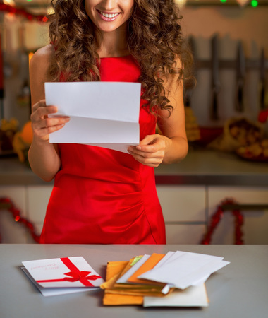 Happy young housewife reading letter in christmas decorated kitchen