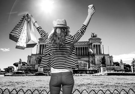 Roman Holiday. Seen from behind trendy tourist woman in the front of Palazzo Venezia in Rome, Italy with shopping bags and coffee cup rejoicing