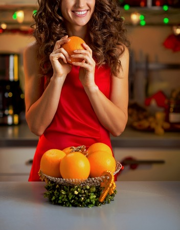 Happy young housewife with oranges in christmas decorated kitchen Stock Photo