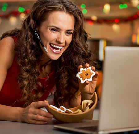 ノート パソコンでビデオ チャットしながらクリスマスのクッキーを示す笑顔の若い女性 写真素材