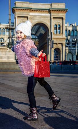 ものを再発見して誰もがミラノで大好きです。楽しんでミラノ、イタリアの赤いショッピング バッグと幸せのエレガントな女の子の完全な長さの肖
