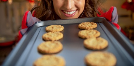 Happy young housewife showing pan with christmas cookies