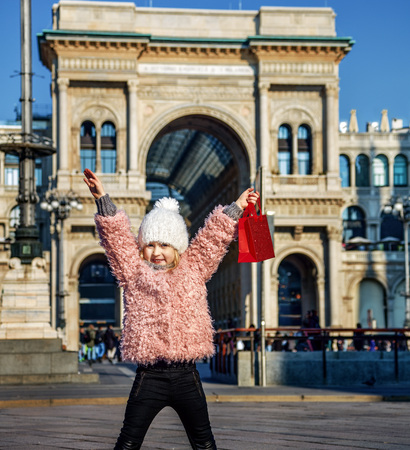 Rediscovering things everybody love in Milan. Full length portrait of smiling elegant girl with red shopping bag near Galleria Vittorio Emanuele II in Milan, Italy rejoicing Stock Photo