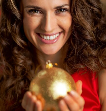 クリスマス ボールを保持している笑顔の若い主婦の肖像画