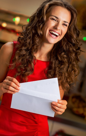 Portrait of happy young housewife with christmas letter in kitchen Stock Photo