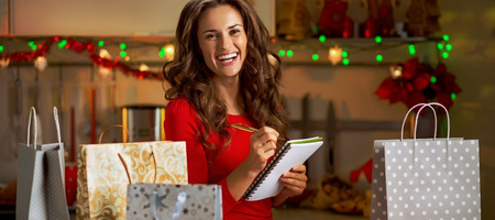 Happy young woman checking list of christmas presents Reklamní fotografie