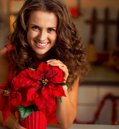 Decorating home on Christmas are wonderful way to enjoy the spirit of the season. Smiling young woman with christmas rose in decorated kitchen