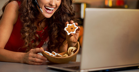 Smiling young woman showing christmas cookies while having video chat on laptop Stok Fotoğraf - 89146305