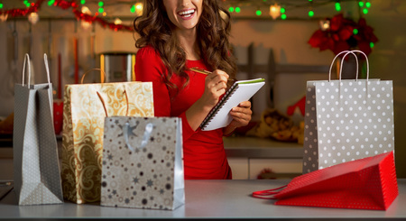Happy young woman checking list of christmas presents Stock Photo
