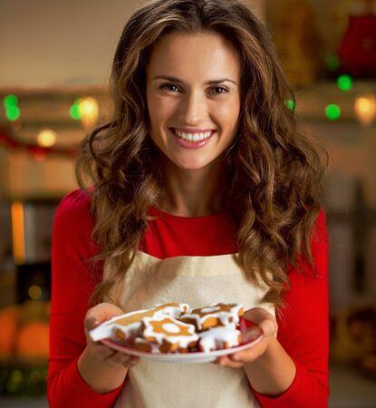 크리스마스 쿠키를 보여주는 행복 젊은 주부