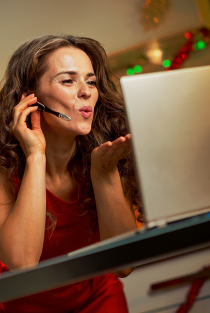 Happy young housewife in red dress having video chat on laptop in christmas decorated kitchen Stok Fotoğraf