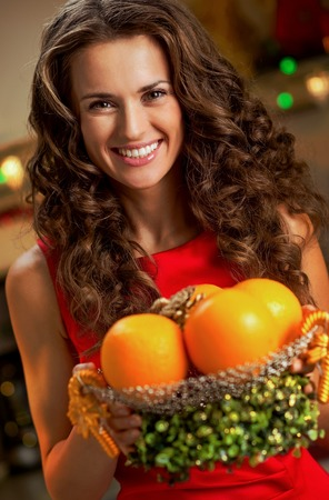 happy young housewife showing plate of oranges Stock Photo