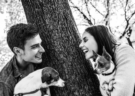 happy young couple with dogs outdoors in autumn park Stock Photo