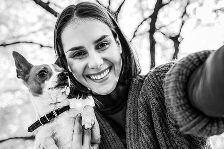 야외에서 개가 함께 셀카 만들기 가을에 웃는 젊은 여자