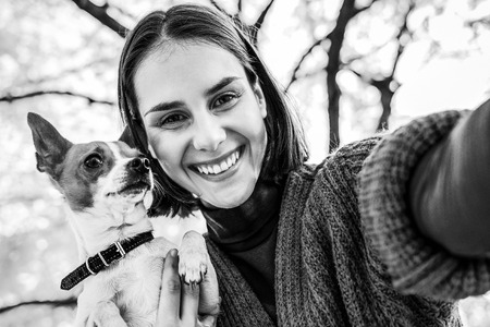 smiling young woman with dog outdoors in autumn making selfie