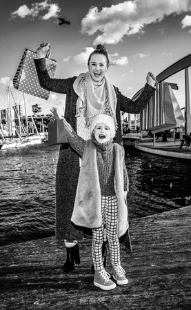in Barcelona for a perfect present. Full length portrait of smiling modern mother and child with shopping bags on embankment in Barcelona, Spain rejoicing