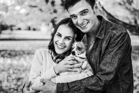 Portrait of happy young couple with dog outdoors in autumn Stock Photo
