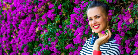 Colorful Freshness. Portrait of smiling trendy woman in  stripy shirt near colorful magenta flowers bed